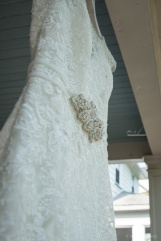 wedding dress hanging in front of house by Sorrells Photography