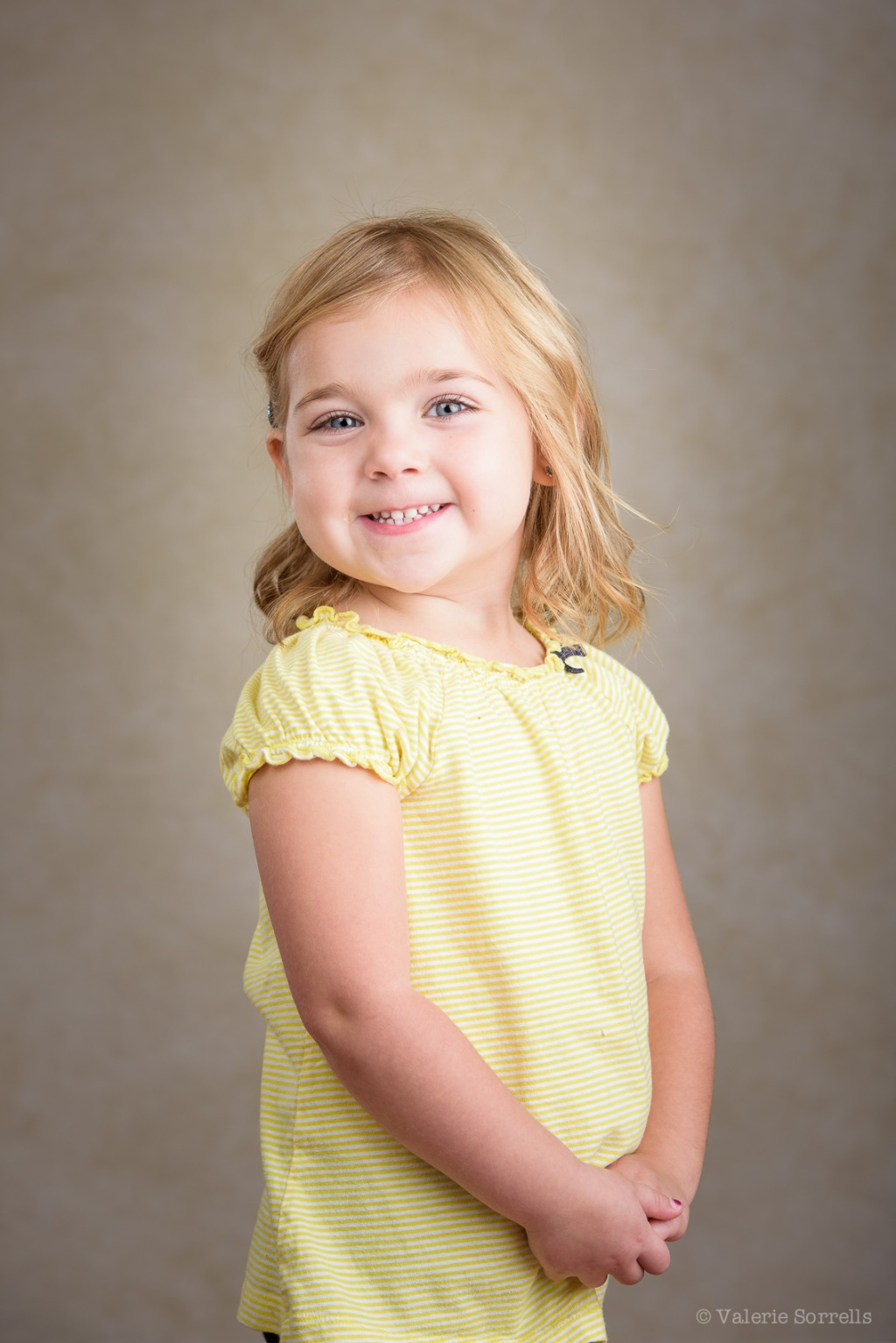 girl in yellow shirt with tan background